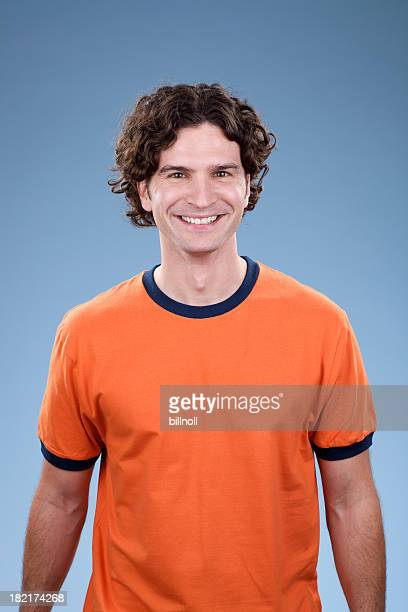 Young smiling man with orange shirt on blue background