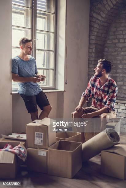 Jeunes hommes souriants au repos et la communication après avoir emménagé dans nouvel appartement.