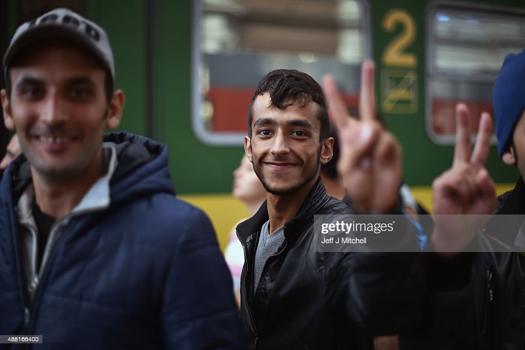 A young smiling migrant man gives a victory sign gesture as he prepares to board a train leaving for the Austrian border at the Keleti railway station on September 14, 2015 in Budapest, Hungary. Migrants who arrive in Budapest overnight gather in the morning at the railway station as they try to be on the early trains leaving Budapest due to fears that the borders will possibly close in the coming days. Since the beginning of 2015 the number of migrants using the so-called 'Balkans route' has exploded with migrants arriving in Greece from Turkey and then travelling on through Macedonia and Serbia before entering the EU via Hungary. The number of people leaving their homes in war torn countries such as Syria, marks the largest migration of people since World War II.