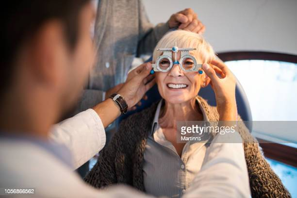 young smiling ophthalmologist checking eyesight of an old woman. - eye test equipment stock pictures, royalty-free photos & images