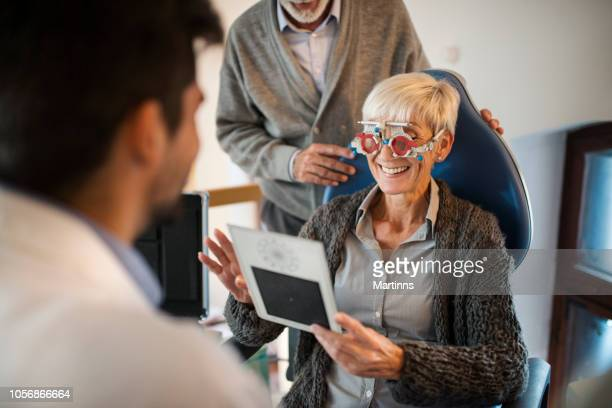 young smiling ophthalmologist checking eyesight of an old woman. - lens optical instrument stock pictures, royalty-free photos & images