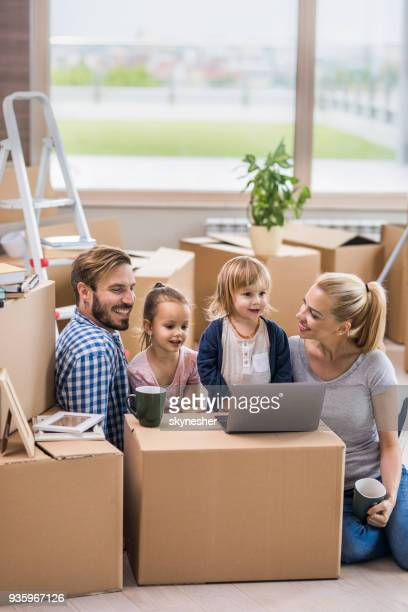 young smiling parents and their small kids using computer while relocating into new home. - penthouse girls stock pictures, royalty-free photos & images