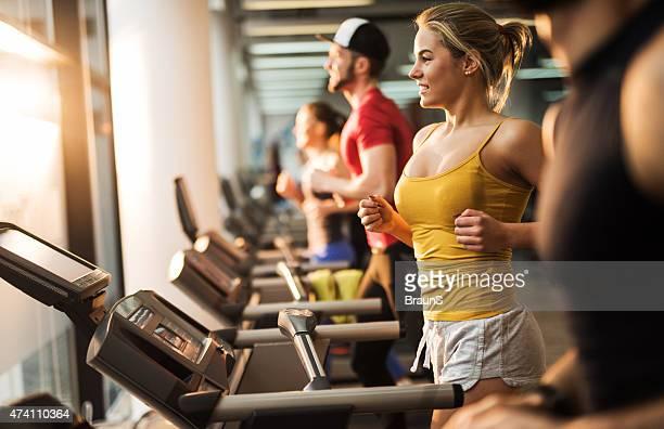 Junge lächelnde Menschen Laufen auf dem Laufband im Fitness-club.