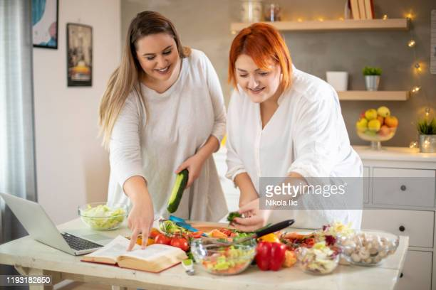 young smiling plus size women preparing salad. - fat nutrient stock pictures, royalty-free photos & images