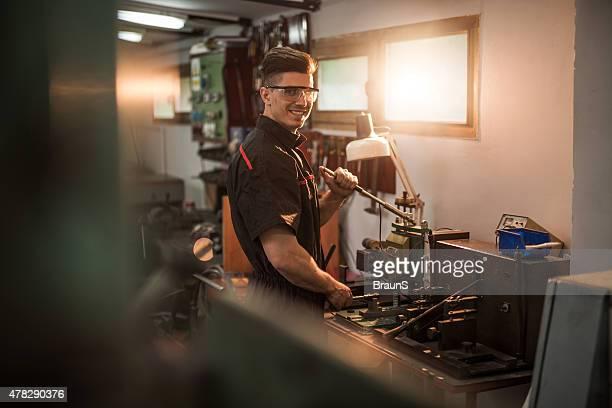 Junge lächelnd Handwerker Arbeiten in der Werkstatt.