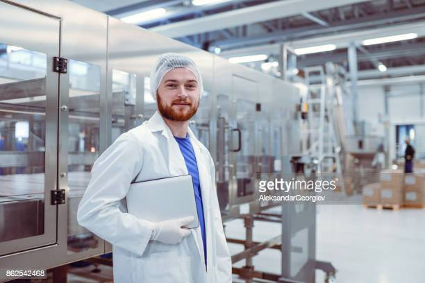 Young Smiling Scientist With Digital Tablet Posing in Factory