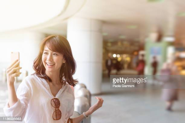 young smiling tourist woman in a mall making a video chat - capturing an image stock pictures, royalty-free photos & images