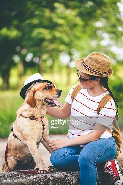 Jeune femme souriante et son chien portant chapeaux