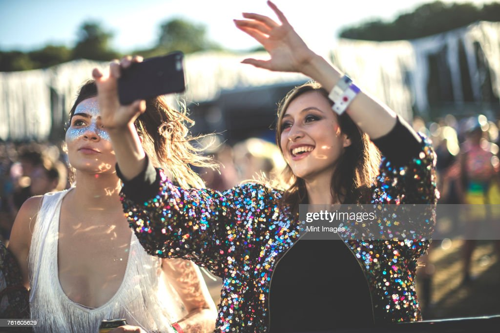 Young smiling woman at a summer music festival wearing multi-coloured sequinned jacket, taking picture with smartphone. : Stock Photo