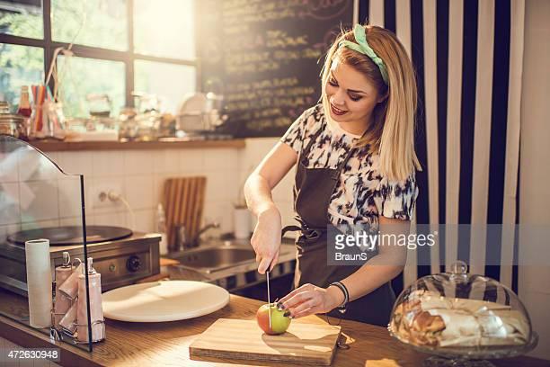 Junge lächelnde Frau Schneiden ein Apfel in ein Essen Platz.