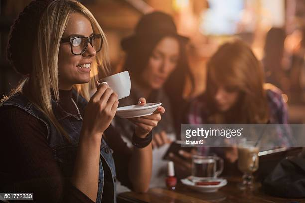 Young smiling woman enjoying in espresso coffee at cafe.