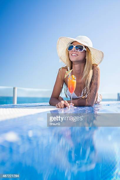 Young smiling woman enjoying in summer cocktail at the pool.