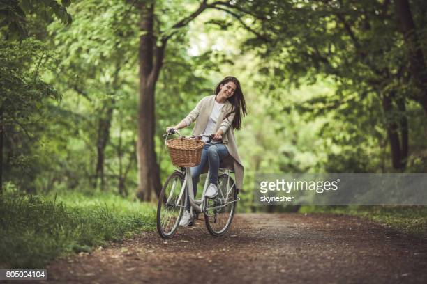 Young smiling woman enjoying on a bike during spring day in nature.