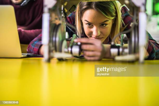young smiling woman examining robotic parts in laboratory. - engineering stock pictures, royalty-free photos & images