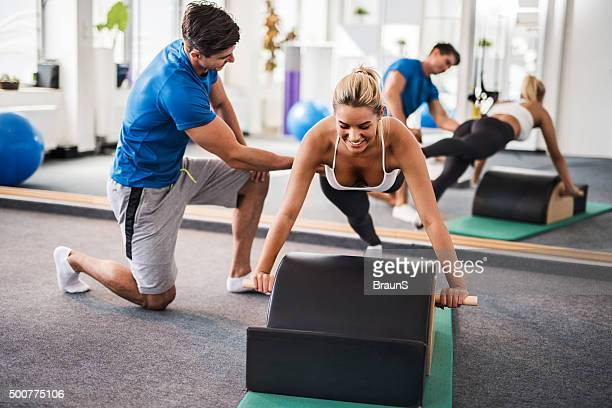 Young smiling woman exercising Pilates with a coach.