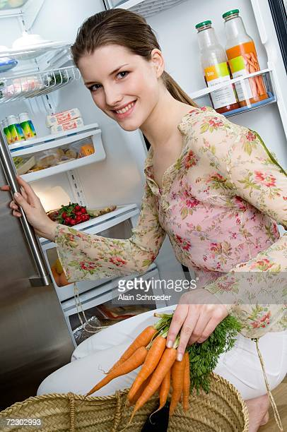 Young smiling woman filling refrigerator, holding carrots