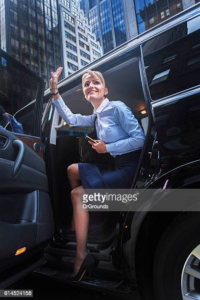 Young smiling woman getting out of car