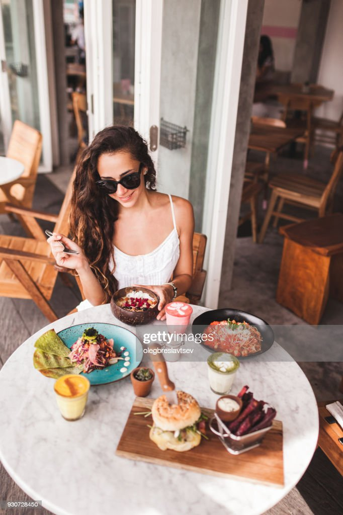 Young smiling woman having breakfast in stylish street cafe. Smoothie bowl, matcha latte, tacos and burger : Stock Photo
