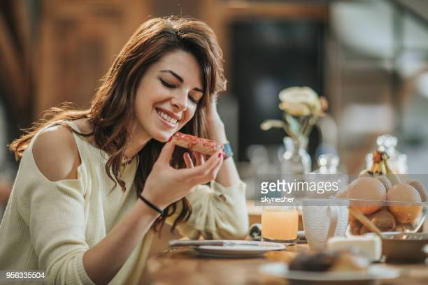 young smiling woman having breakfast in the kitchen. - jam stock pictures, royalty-free photos & images