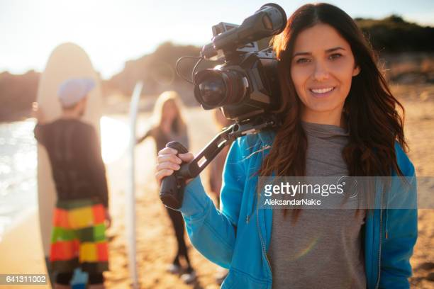 young smiling woman holding video camera - cinematographer stock pictures, royalty-free photos & images