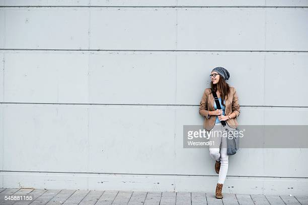 Young smiling woman leaning against a wall waiting