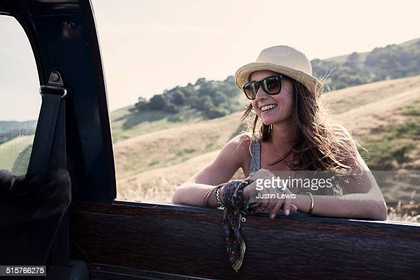 Young smiling woman leans on truck in a field