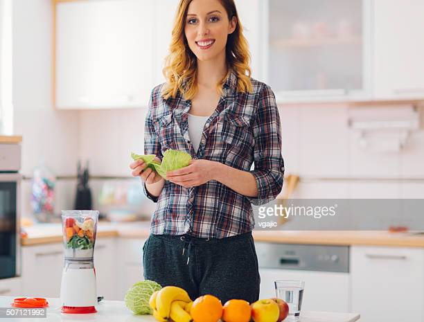 Young Smiling Woman making smoothie.