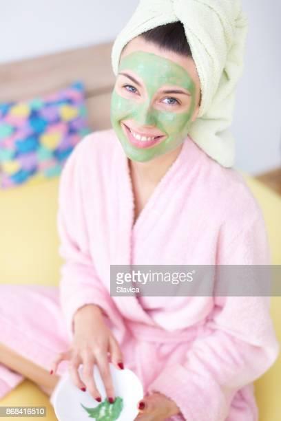 Junge lächelnde Frau setzen Gesichtsmaske zu Hause