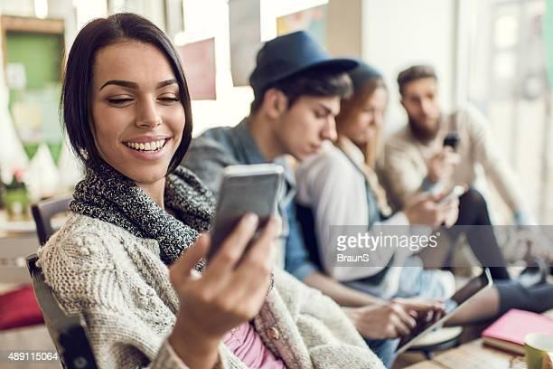 Jovem mulher sorridente ler uma mensagem de texto no telefone móvel.