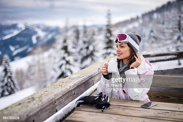 young smiling woman relaxing in a cafe at ski resort. - ski resort stock pictures, royalty-free photos & images