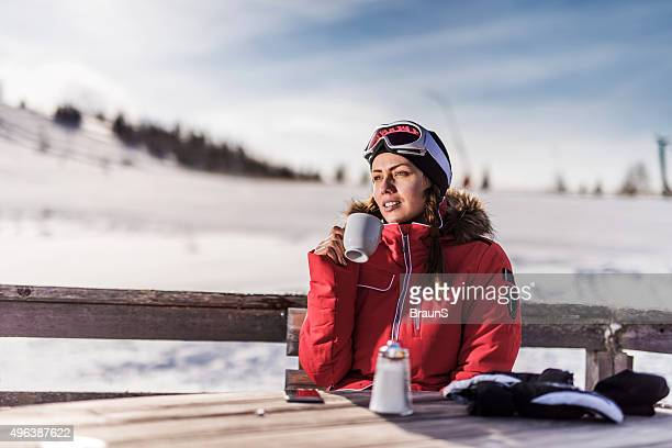 Young smiling woman relaxing in a cafe at ski resort.