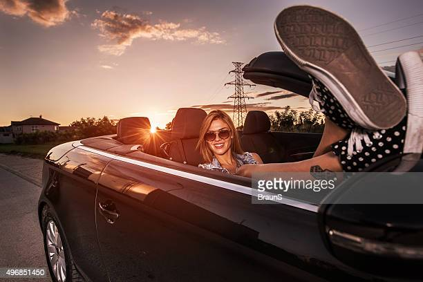 Young smiling woman relaxing in convertible car at sunset.