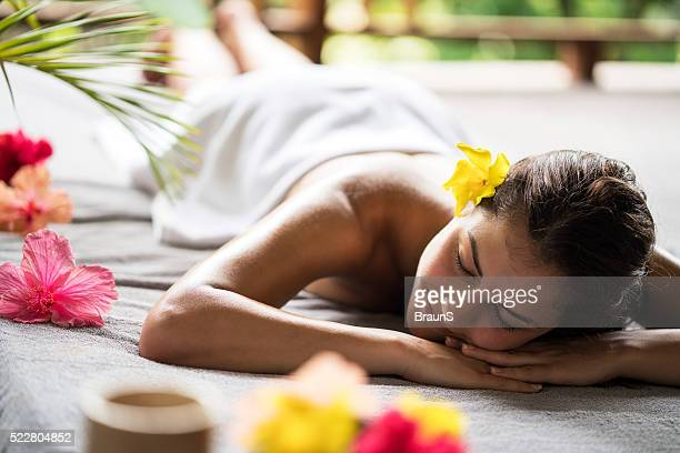 Young smiling woman relaxing on a bed at the spa.