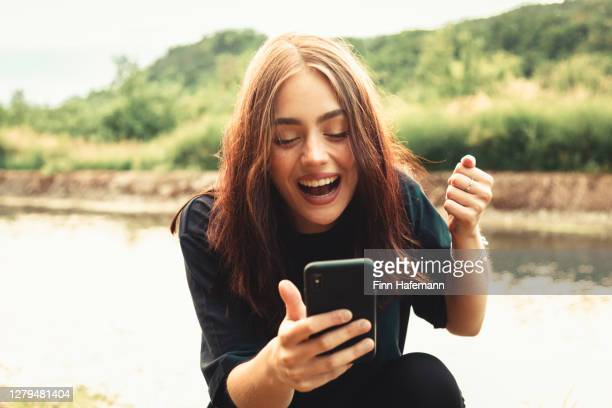 junge lächelnde frau sitzt neben einem fluss typisiert nachrichten auf ihrem smartphone - weiblicher teenager stock-fotos und bilder