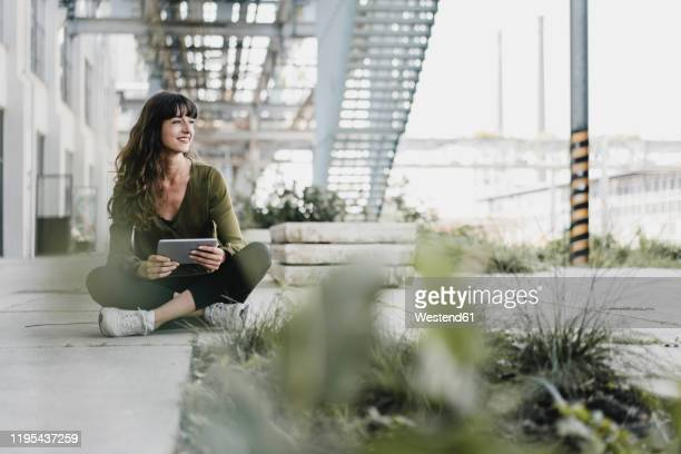 young smiling woman sitting on the ground and using tablet - grün stock-fotos und bilder