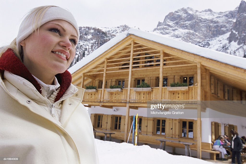 Young, Smiling Woman Standing in Front of a Holiday Home in the Mountains : Stock Photo