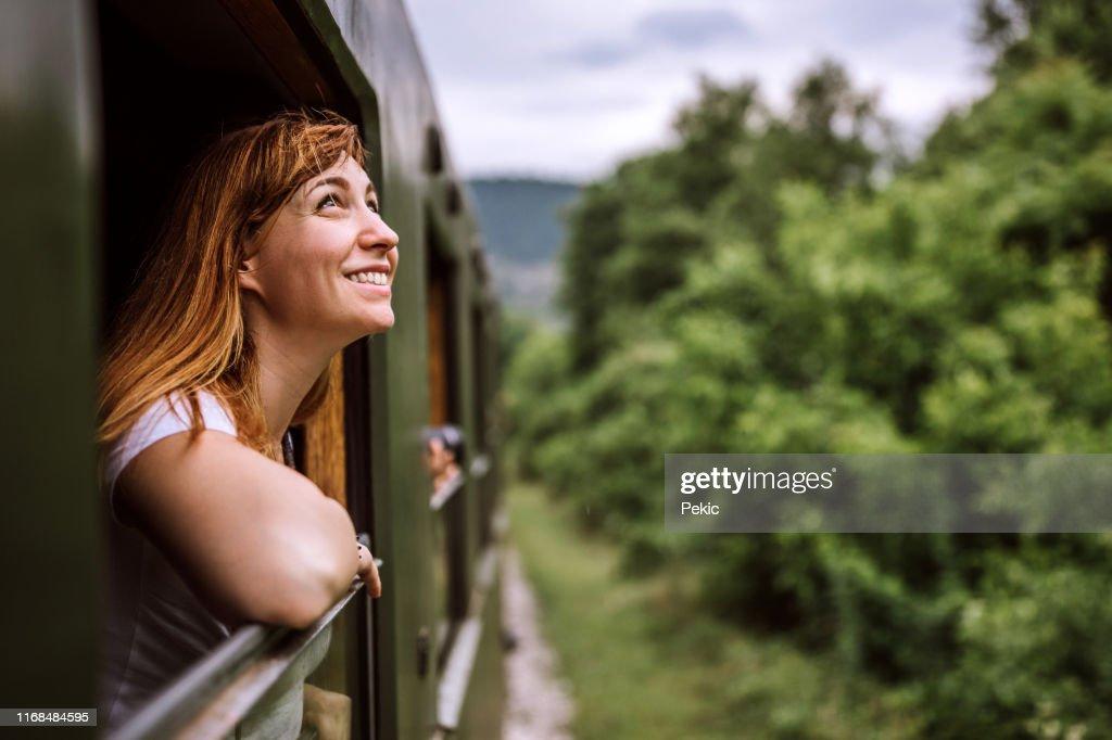 Jonge lachende vrouw staand uit het trein venster tijdens het reizen : Stockfoto