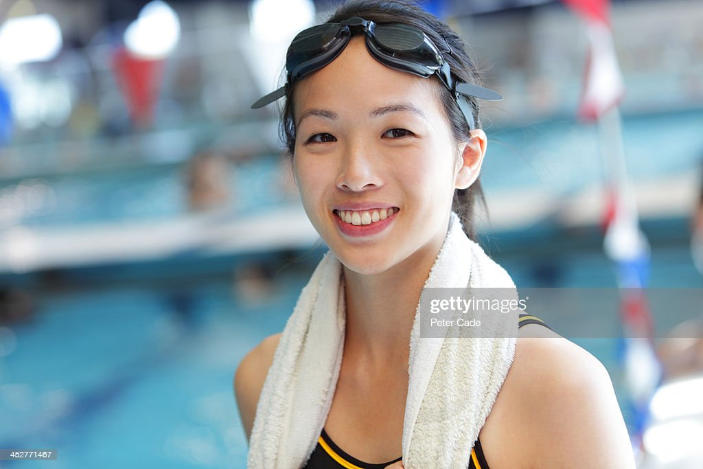 Young smiling woman stood by swimming pool : Stock Photo
