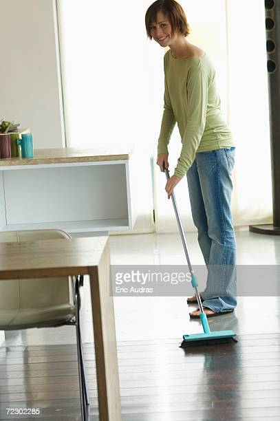 Young smiling woman sweeping living-room floor