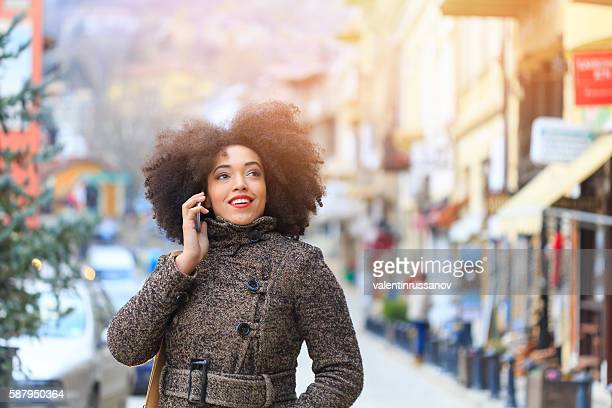 Young smiling woman talking on the phone at street