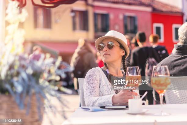 young smiling woman tourist drinking typical spritz aperitif on burano island, venice, italy, city of romance, typical venetian sights, travel destination, wanderlust, happiness, travel, tourism, exploration, vacations, springtime, holiday, solo traveler, - laguna di venezia foto e immagini stock