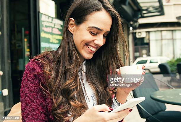 Young smiling woman using smart phone in the coffee shop