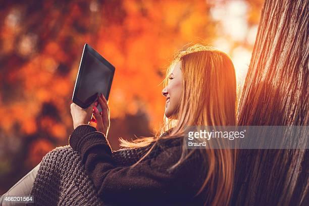 Junge lächelnde Frau mit touchpad im Herbst.