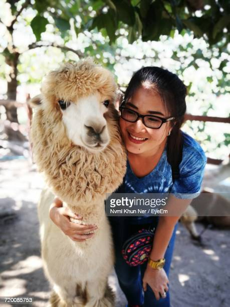 Young Smiling Woman With Alpaca Under Tree
