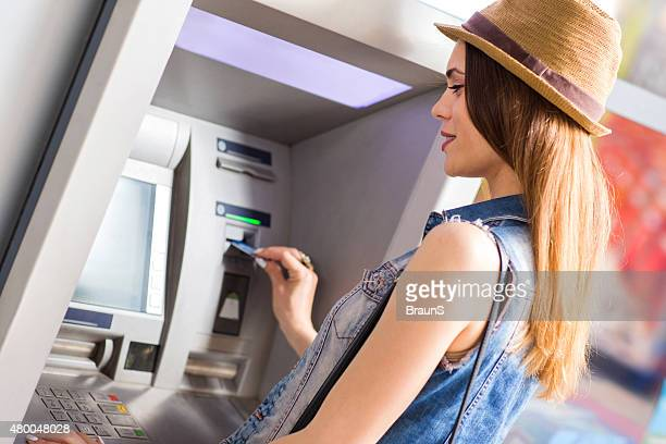 Young smiling woman withdrawing money from ATM.