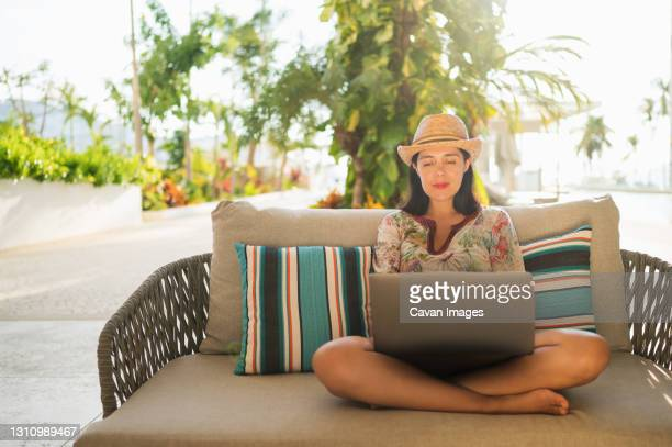 young smiling woman working on laptop in the yard of her house. - ゲレーロ州 ストックフォトと画像