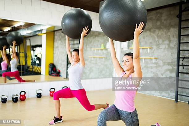Young smiling women doing lunges with fitness ball.