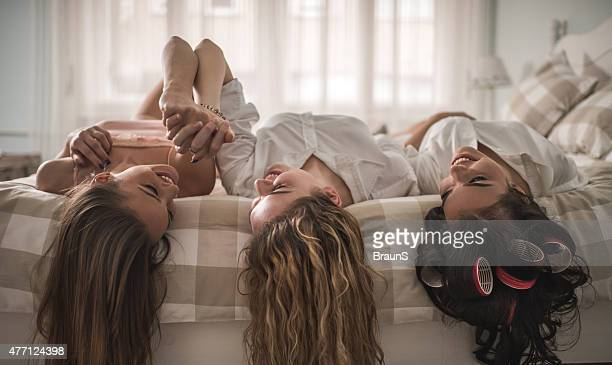 young smiling women relaxing together on bed and communicating. - night in stock pictures, royalty-free photos & images