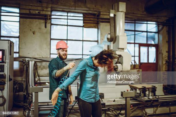 Young Smiling Worker Blow the Sawdust of a Young Female Carpenter with Air Compressor in a Wood Factory