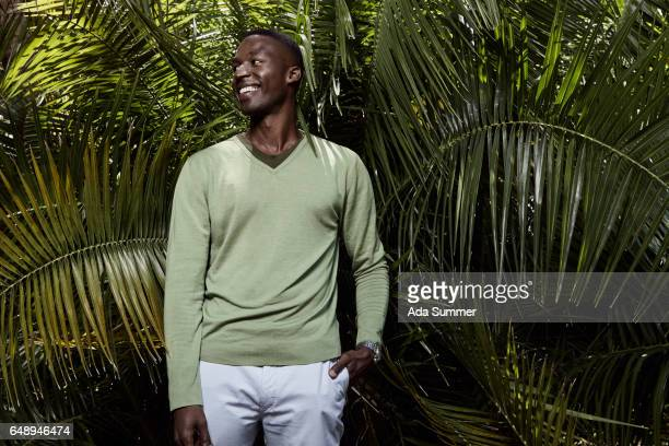 young smilling man in front of a palm tree - vネック ストックフォトと画像